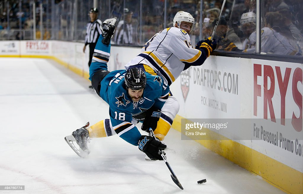 Mike Brown #18 of the San Jose Sharks flips over Mattias Ekholm #14 of the Nashville Predators as he goes for the puck at SAP Center on October 28, 2015 in San Jose, California.