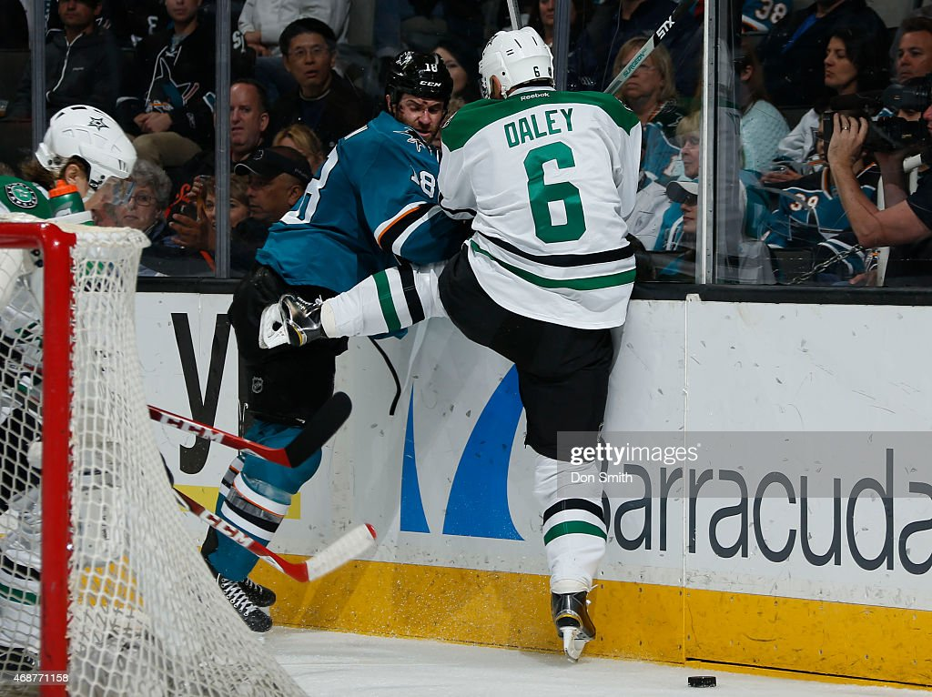 Mike Brown #18 of the San Jose Sharks gets a board check against Trevor Daley #6 of the Dallas Stars at the SAP Center on April 6, 2015 in San Jose, California.