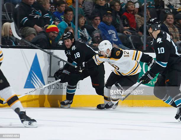 Mike Brown of the San Jose Sharks skates after the puck against Simon Gagne of the Boston Bruins during an NHL game on December 4, 2014 at SAP Center...