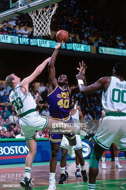 Mike Brown of the Utah Jazz drives to the basket against Larry Bird and Robert Parish of the Boston Celtics during a game played in 1992 at the...