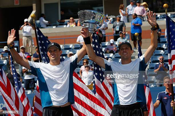 Mike Bryan and Bob Bryan of United States pose with the champions trophy after their 100th career title win after defeating Marcel Granollers and...