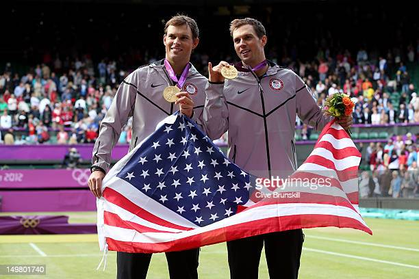 Mike Bryan and Bob Bryan pose with their gold medals and American flag after defeating JoWilfried Tsonga and Michael Llodra of France in their Men's...