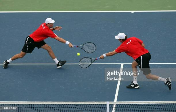 Mike Bryan and Bob Bryan stretch for a volley against Nenad Zimonjic of Serbia and Daniel Nestor of Canada in the Doubles Final during day seven of...