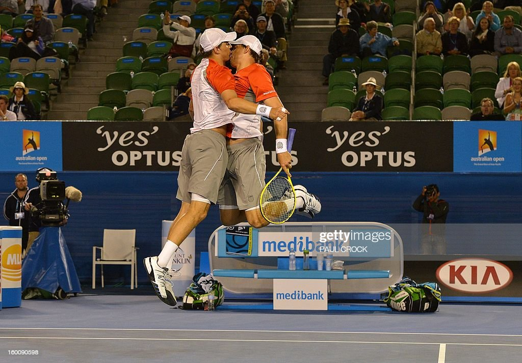 Mike Bryan (L) and his brother Bob of the US celebrate after their victory over the Netherland's Robin Haase and Igor Sijsling during the men's doubles final on day 13 of the Australian Open tennis tournament in Melbourne early on January 27, 2013.