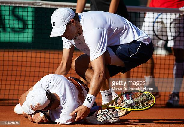 Mike Bryan is helped by his brother Bob Bryan during day two of the semi final Davis Cup between Spain and the United States at the Parque Hermanos...