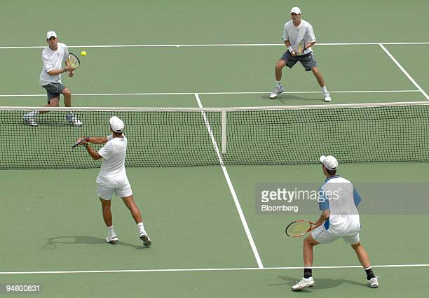 Mike Bryan of the United States left partnered with his brother Bob Bryan returns the ball to Jeff Coetzee of South Africa bottom left and Rogier...
