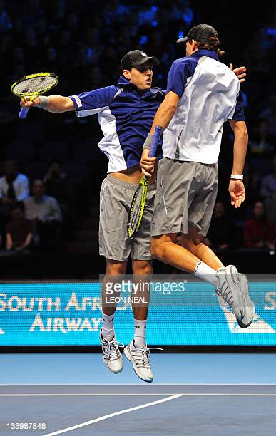 Mike Bryan of the US and his partner Bob Bryan of the US do their trademark chest bump in celebration after beating Robert Lindstedt of Sweden and...
