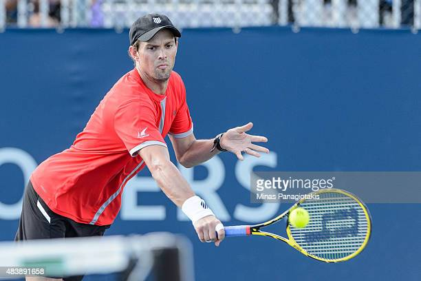 Mike Bryan of the USA hits a return against Feliciano Lopez of Spain and Max Mirnyi of Belarus during day four of the Rogers Cup at Uniprix Stadium...