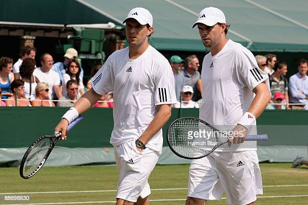 Mike Bryan of USA talks tactics with Bob Bryan of USA during the men's doubles second round match against Johan Brunstrom of Sweden and JeanJulien...