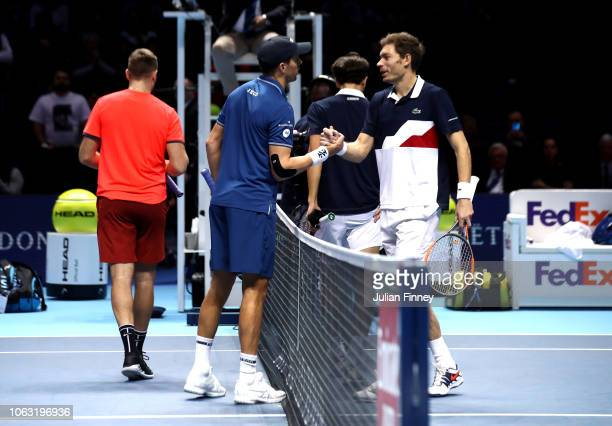 Mike Bryan partner of Jack Sock of The United States shakes hands with Nicolas Mahut partner of Pierre-Hugues herbert of France during Day Eight of...