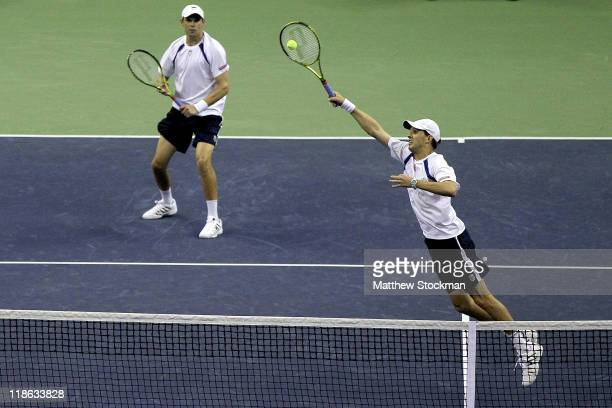 Mike Bryan retunrs a shot to Fernando Verdasco and Marcel Granollers of Spain while playing with Bob Bryan during the third rubber of the Davis Cup...