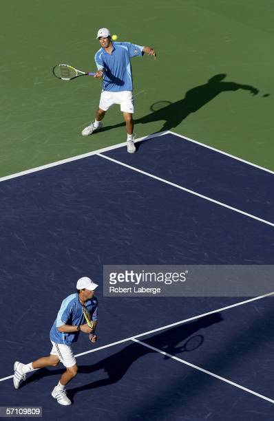 Mike Bryan returns a forehand as his brother Bob Bryan runs to the net in their match against Sebastian Grosjean and Richard Gasquet of France during...