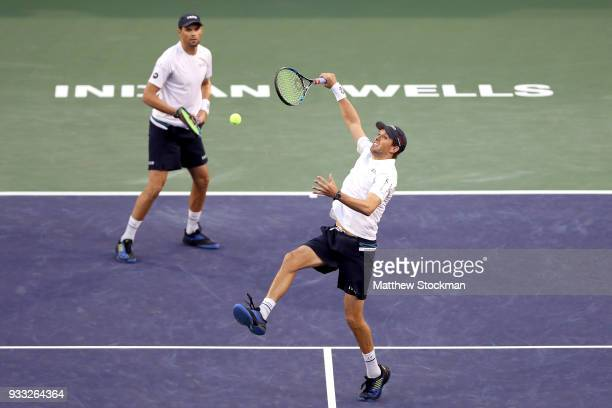 Mike Bryan returns a shot to John Isner and Jack Sock while playing with Bob Bryan during the men's doubles final on Day 13 of the BNP Paribas Open...