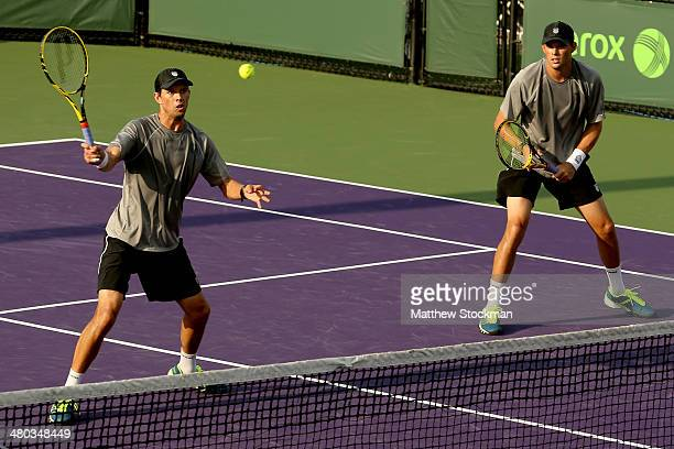 Mike Bryan returns a shot to Olivier Marach of Austria and Dmitry Tursunov of Russia while playing with Bob Bryan during the Sony Open at the Crandon...