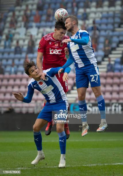 Mike Calveley of Chorley FC goes up for a header with Kyle Joseph and Tom James of Wigan Athletic during the FA Cup First Round match between Wigan...