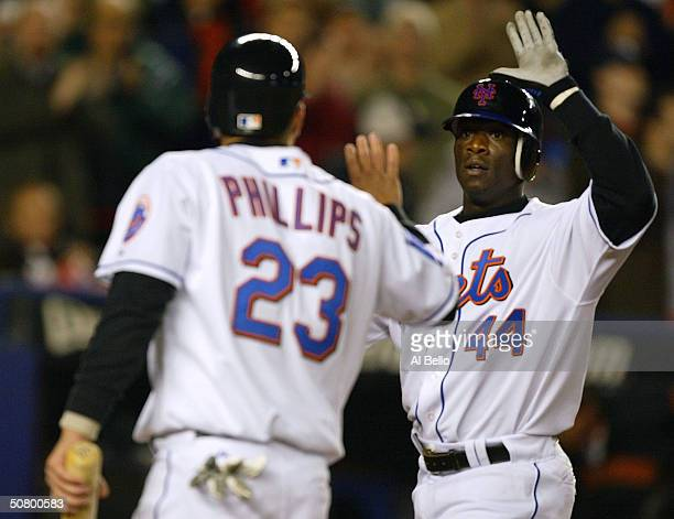 Mike Cameron of the New York Mets is greeted by Jason Phillips at home plate after hitting a 2-run home run that against the San Fransisco Giants in...