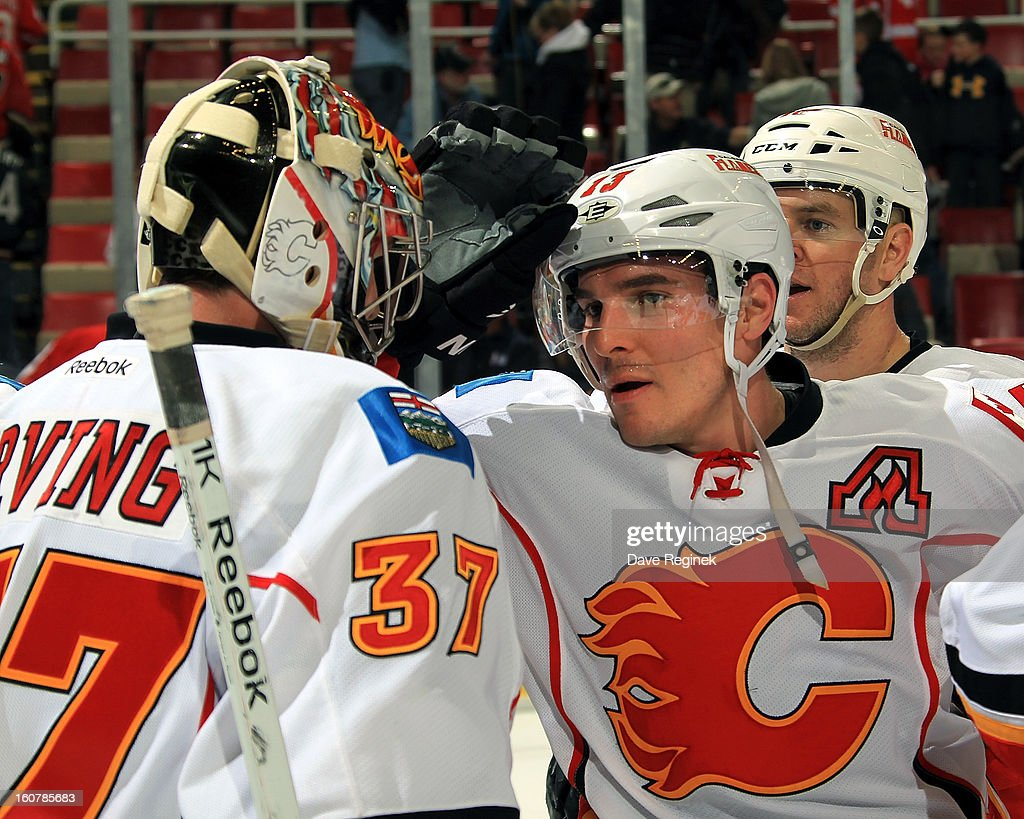 Mike Cammalleri #13 and goalie Leland Irving #37 of the Calgary Flames celebrate after a NHL game against the Detroit Red Wings at Joe Louis Arena on February 5, 2013 in Detroit, Michigan. Calgary defeated Detroit 4-1