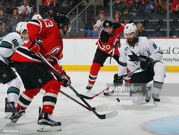 Mike Cammalleri and Lee Stempniak of the New Jersey Devils converge on Brent Burns of the San Jose Sharks during the second period at the Prudential...