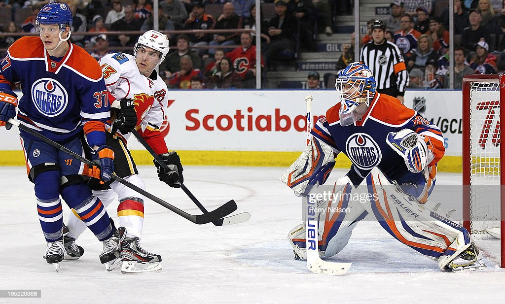 Mike Cammalleri #13 of the Calgary Flames and Lennart Petrell #37 of the Edmonton Oilers battle for position in front of Devan Dubnyk #40 of the Edmonton Oilers at Rexall Place on April 1, 2013 in Edmonton, Alberta, Canada.