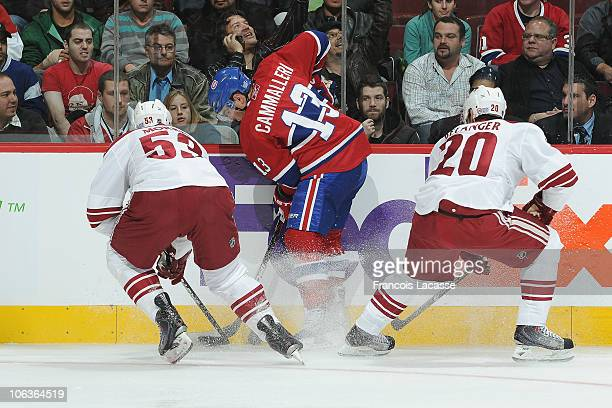 Mike Cammalleri of the Montreal Canadiens battles for the puck along the borads with Derek Morris and Eric Belanger of the Phoenix Coyotes during the...