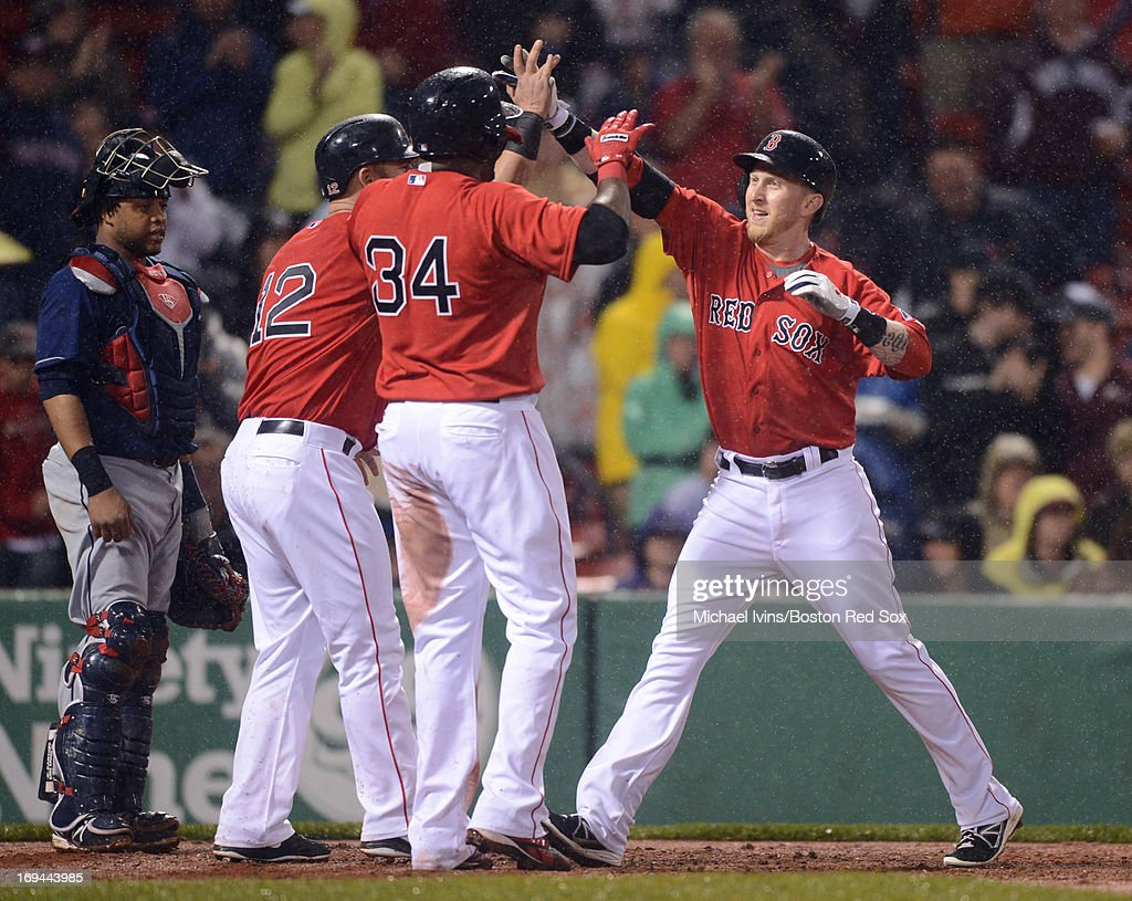 Mike Carp #37 of the Boston Red Sox is greeted by David Ortiz #34 and Mike Napoli #12 after hitting a three-run home run against the Cleveland Indians in the third inning on May 24, 2013 at Fenway Park in Boston, Massachusetts.