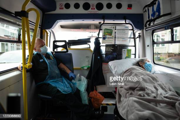 Mike Carr of the Patient Transport Services of South Central Ambulance Services looks towards an elderly non-COVID-19 patient as she is moved from...