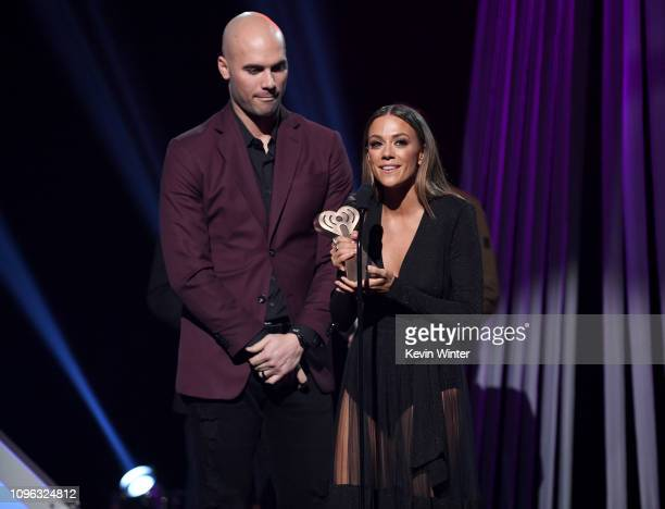 Mike Caussin and Jana Kramer receive award onstage at the 2019 iHeartRadio Podcast Awards Presented by Capital One at the iHeartRadio Theater LA on...
