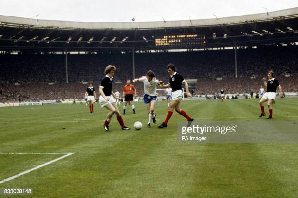 Mike Channon, the England forward, tries to go through Francis Munro and Gordon McQueen of Scotland