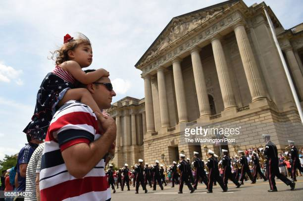 Mike Chatterelli and his daughter Lucia Chatterelli of Bethesda MD watch the National Memorial Day Parade on Monday May 25 2015 in Washington DC