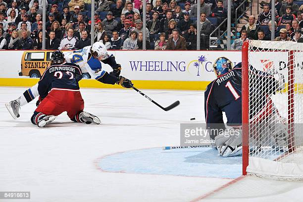 Mike Commodore of the Columbus Blue Jackets checks T.J. Oshie of the St. Louis Blues, breaking up a scoring chance during a St. Louis Blues power...