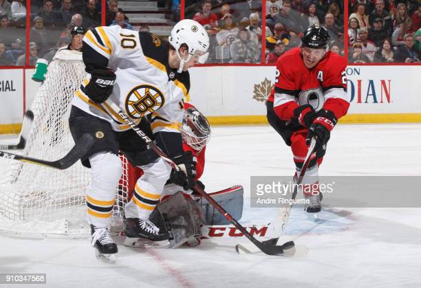 Mike Condon and Dion Phaneuf of the Ottawa Senators defend their net against a scoring chance by Anders Bjork of the Boston Bruins at Canadian Tire...