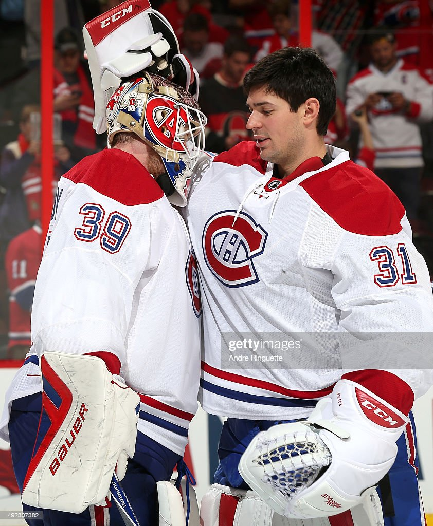 Mike Condon #39 of the Montreal Canadiens celebrates his first career NHL win with teammate Carey Price #31 after a game against the Ottawa Senators at Canadian Tire Centre on October 11, 2015 in Ottawa, Ontario, Canada.