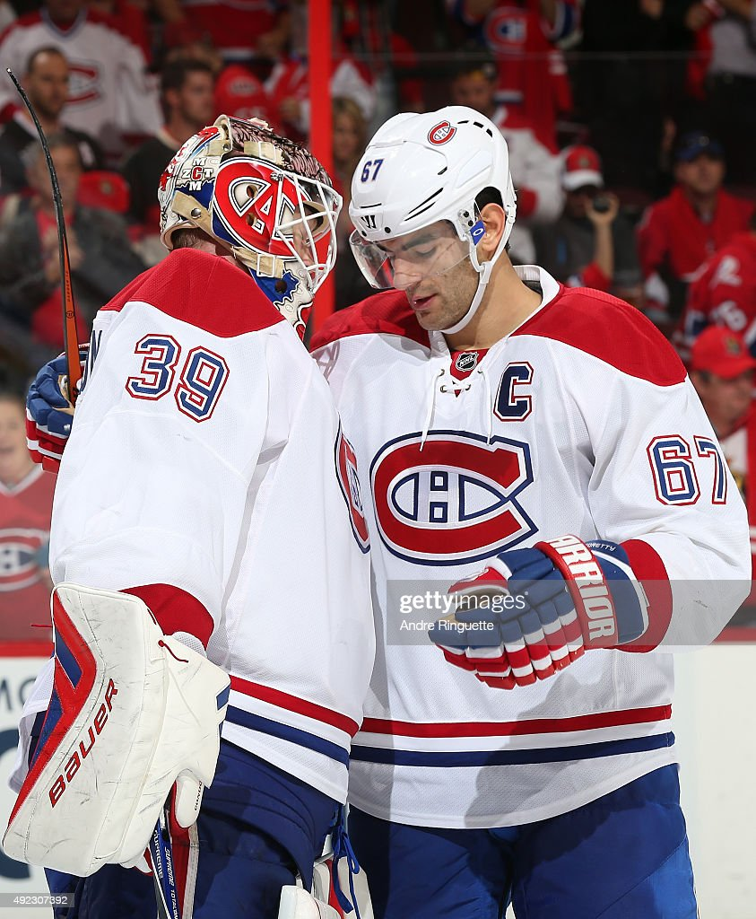 Mike Condon #39 of the Montreal Canadiens celebrates his first career NHL win with teammate Max Pacioretty #67 after a game against the Ottawa Senators at Canadian Tire Centre on October 11, 2015 in Ottawa, Ontario, Canada.