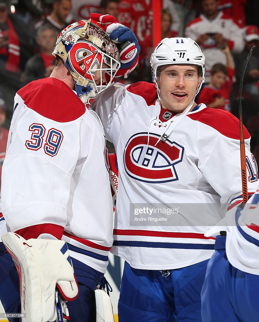 Mike Condon #39 of the Montreal Canadiens celebrates his first career NHL win with teammate Brendan Gallagher #11 after a game against the Ottawa Senators at Canadian Tire Centre on October 11, 2015 in Ottawa, Ontario, Canada.