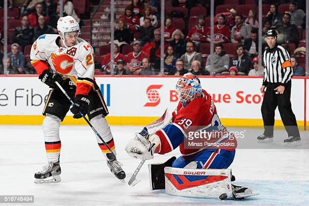 Mike Condon of the Montreal Canadiens makes a pad save near Sean Monahan of the Calgary Flames during the NHL game at the Bell Centre on March 20...