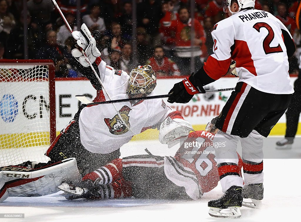 Mike Condon #1 of the Ottawa Senators makes a save off of his gloves as Marcus Kruger #16 of the Chicago Blackhawks crashes into him after being shoved down by Dion Phaneuf #2 at the United Center on December 20, 2016 in Chicago, Illinois. The Senators defeated the Blackhawks 4-3.