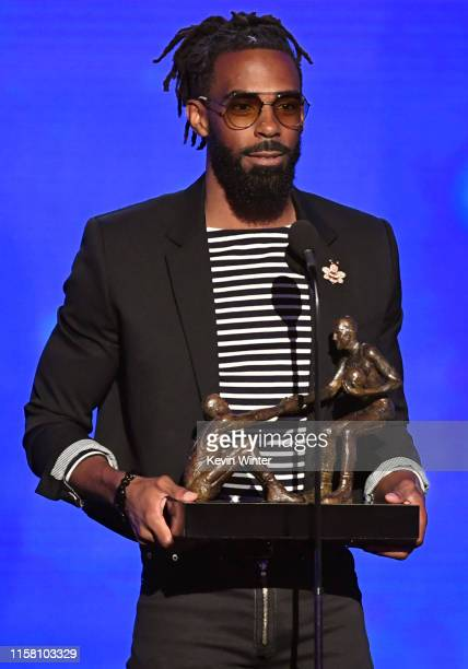 Mike Conley Jr accepts the NBA TwymanStokes Teammate of the Year Award onstage during the 2019 NBA Awards presented by Kia on TNT at Barker Hangar on...