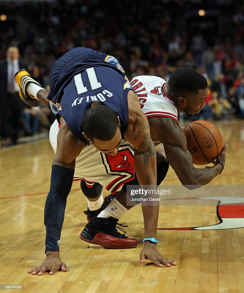 Mike Conley #11 of the Memphis Grizzles falls over Nate Robinson #2 of the Chicago Bulls at the United Center on January 19, 2013 in Chicago, Illinois. The Grizzlies defeated the Bulls 85-82 in overtime.
