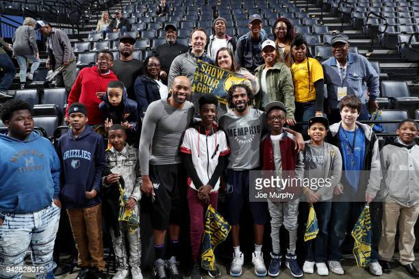 Mike Conley of the Memphis Grizzlies and Vince Carter of the Sacramento Kings pose with a fan for a photo before the game on April 6 2018 at...