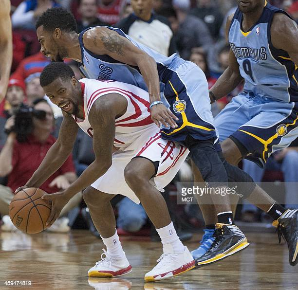 Mike Conley of the Memphis Grizzlies goes over the back of Aaron Brooks of the Houston Rockets for a foul in the second half of the Rockets' 100-92...
