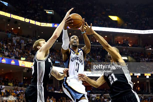 Mike Conley of the Memphis Grizzlies goes up for a shot between Matt Bonner and Tim Duncan of the San Antonio Spurs in the first half during Game...
