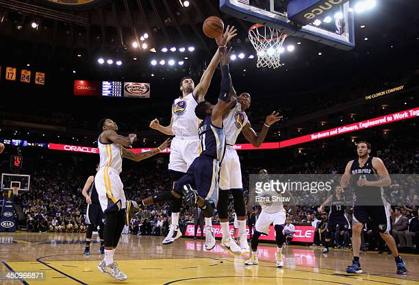 Mike Conley of the Memphis Grizzlies has a shot blocked by Andrew Bogut and Marreese Speights of the Golden State Warriors at ORACLE Arena on...