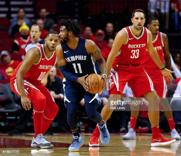 Mike Conley of the Memphis Grizzlies is guarded by Eric Gordon of the Houston Rockets and Ryan Anderson at Toyota Center on October 23 2017 in...