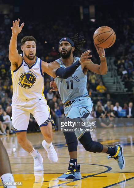 Mike Conley of the Memphis Grizzlies passes the ball away from Klay Thompson of the Golden State Warriors during an NBA basketball game at ORACLE...