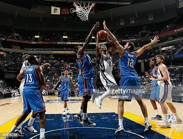 Mike Conley of the Memphis Grizzlies puts up a shot between Jeff Green and Nenad Krstic of the Oklahoma City Thunder during the preseason game on...