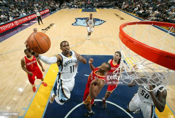 Mike Conley of the Memphis Grizzlies shoots a layup against Chuck Hayes of the Houston Rockets on January 21 2011 at FedExForum in Memphis Tennessee...