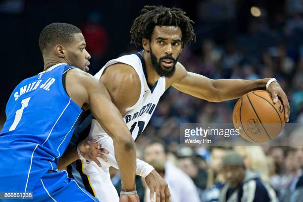 Mike Conley of the Memphis Grizzlies with the ball and being guarded by Dennis Smith Jr #1 of the Dallas Mavericks at the FedEx Forum on October 26...