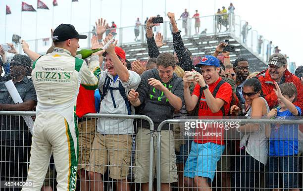 Mike Conway of England driver of the Ed Carpenter Racing Dallara Chevrolet winner, sprays champagne on the crowd at the podium ceremony during race 2...