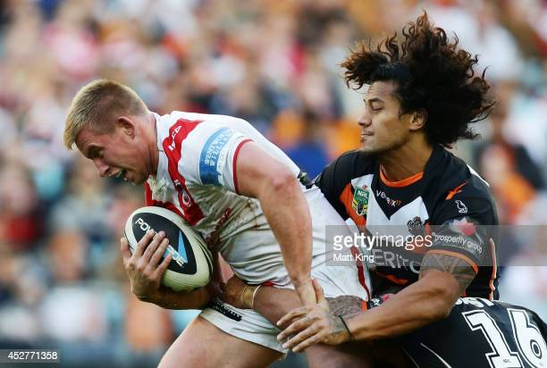 Mike Cooper of the Dragons is tackled during the round 20 NRL match between the Wests Tigers and the St George Illawarra Dragons at ANZ Stadium on...
