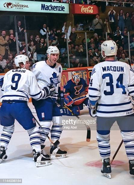Mike Craig Dave Andreychuk and Jamie Macoun of the Toronto Maple Leafs celebrate against Curtis Joseph and the St Louis Blues during NHL game action...